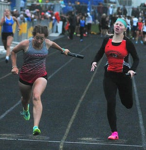 Loudonville's Sydney Polen (left) crosses the finish line during the 4x100 relay Friday at the Division III Massillon Regional.