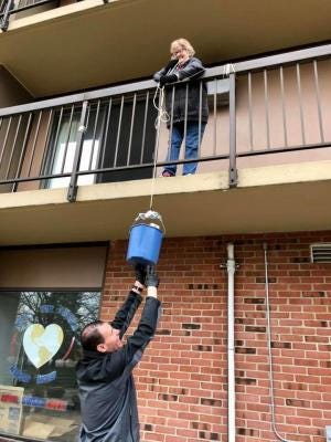 A Monroe County Opportunity Program staff member hoists food up to a senior resident at the Mable Kehres Apartment Complex in Monroe Township in April. The resident was concerned about possible exposure to COVID-19, so MCOP rigged a pulley system to deliver food while maintaining social distancing.