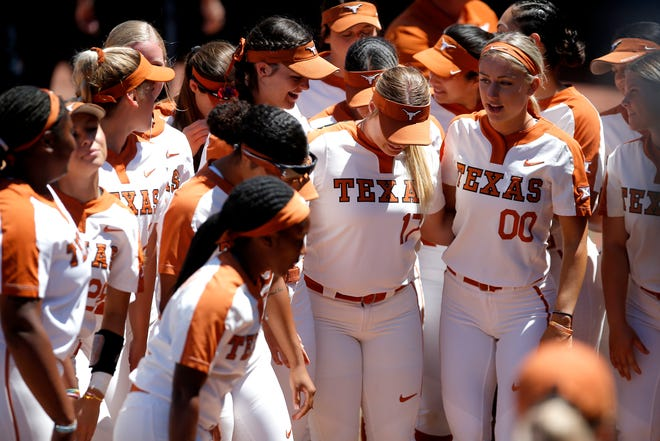 Texas players huddle before the start of Saturday's NCAA softball super regional against Oklahoma State in Stillwater, Okla. The Longhorns won 4-2 to force the decisive third game on Sunday.