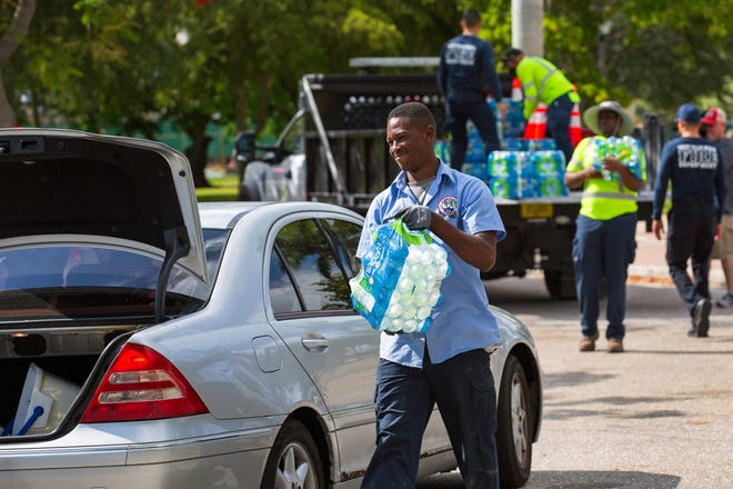 Corey Robinson of the City of West Palm Beach water distribution department,works with firefighters and workers with several other departments to hand out bottled water to residents at Gaines Park on Saturday morning. The city issued an advisory that infants, young children and other vulnerable people in the city, as well as the towns of Palm Beach and South Palm, should not drink the tap water after discovering a toxin produced by blue-green algae in its water supply.