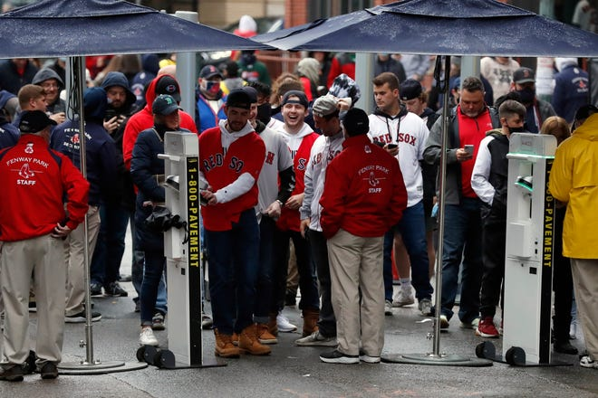 Fans line up to pass through security at the entrance to Fenway Park before a baseball game between the Boston Red Sox and the Miami Marlins on May 29, 2021, in Boston. Saturday marked the end of most COVID-19 restrictions in Massachusetts.