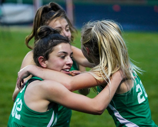 Brook McIntyre, right, Katie Lane, left, and Rachel Whetstone, back, celebrate a second-place finish in the 4x400 relay at the regional finals hosted by Massillon Perry High School on May 28, 2021.