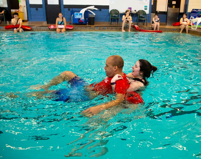 Lifeguard instructor Madison Harms, right, demonstrates proper technique to students with fellow instructor Victor Tilghman during a certification class for prospective lifeguards at the Eugene Family YMCA in Eugene.