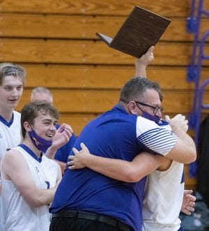 Jackson's head coach Mike Ryan hugs Bryce Layman as he holds up the Division I regional final trophy after defeating Stow on Saturday, May 29, 2021. (Bob Rossiter / Special to The Canton Repository)