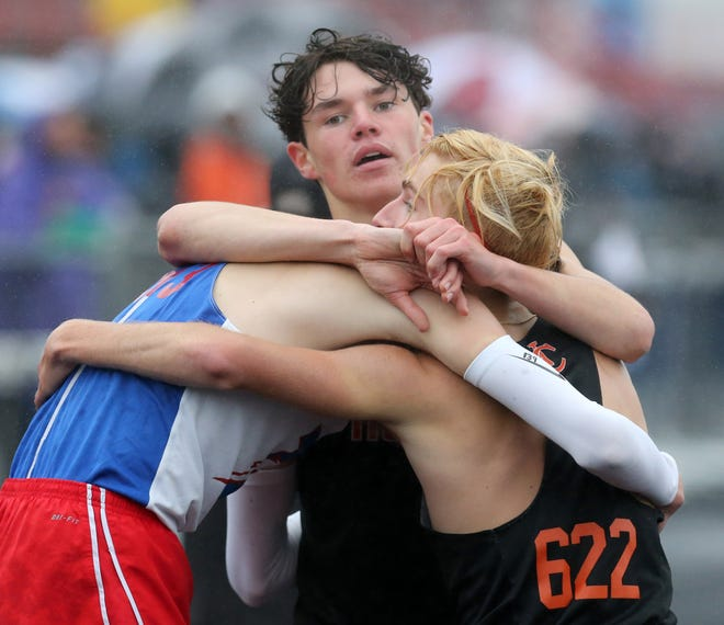 Hoover's Noah Johnson (top), Lake's Connor Wertman (left) and Hoover's Blaze Fichter (right) embrace after the boys 1,600-meter run at Friday's Division I regional track and field meet. Fichter finished first, Wertman came in second and Johnson was fourth.