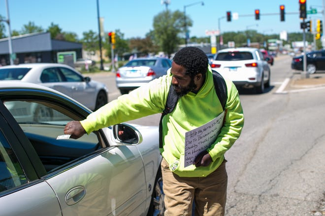 Kelsey Rogers receives money from a motorist at the corner of East State Street and Alpine Road Saturday, May 29, 2021, in Rockford. Rogers says he is looking for employment but is struggling to obtain a state-issued identification card and his birth certificate from another state.