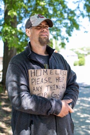 William Clark asks for money from motorists at the corner of 9th Street and E State Street Saturday, May 29, 2021, in Rockford.