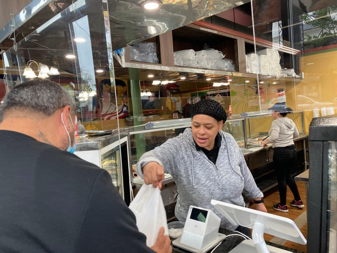 Veronica Vargas hands a customer a takeout order at Ajo Y Cilantro restaurant on Main Street Saturday, the first day most statewide COVID-19 restrictions were lifted.