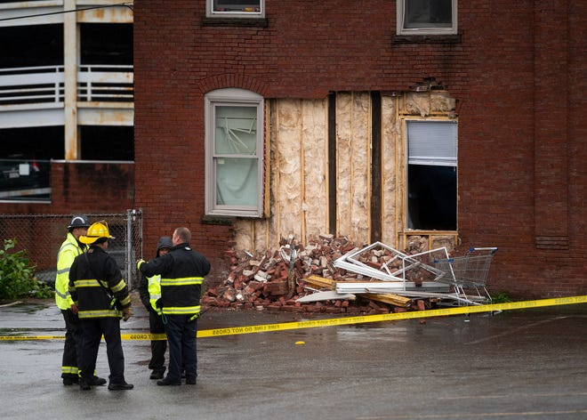 Members of the Worcester Fire Department assess a partial building collapse Saturday on Irving Street.