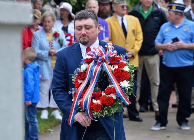 Sharpsburg Vice Mayor Jacob Martz lays a wreath at war monuments in public square Saturday during the town's Memorial Day commemorations.