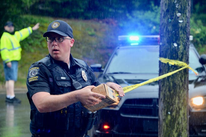 A police officer hangs police tape to close a street where a suspect in an earlier death exchanged gunfire with police in Martinsburg on Friday afternoon.