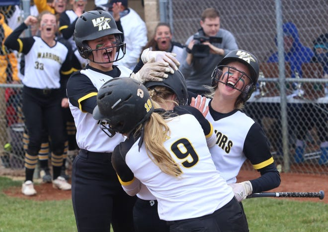 McKayla Jellison, center, is mobbed by her teammates after hitting a home run to give Watkins Memorial a 3-1 lead over Pickerington Central in a Division I softball regional final last Saturday.