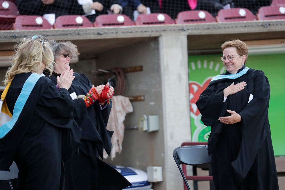 Retiring athletic director Kathy Bates, right, is honored during the Xavier High School commencement ceremony May 28 at Neuroscience Group Field at Fox Cities Stadium in Grand Chute.