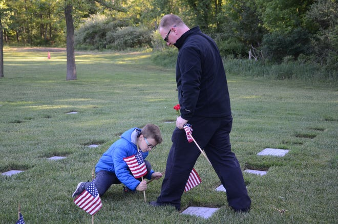 Christian Schuster of Battle Creek shows his son, Alex, 10, where to place a flag on Saturday at Fort Custer National Cemetery.