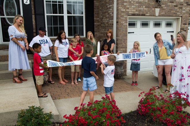Sierra Connolly (far left) watches as family and friends celebrate the announcement that the family's Clarksville home mortgage was paid of by the Tunnel to Towers Foundation, part of its imitative to honor the families of fallen military and first responders by paying off 200 mortgages in 2021.