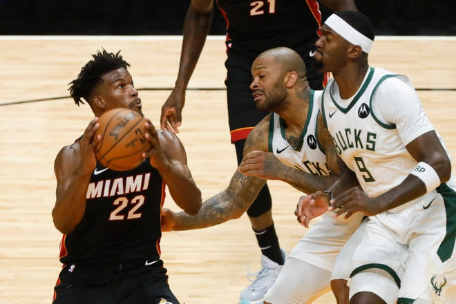 Miami Heat forward Jimmy Butler is guarded by  Bucks center Bobby Portis (9) and forward P.J. Tucker Saturday.