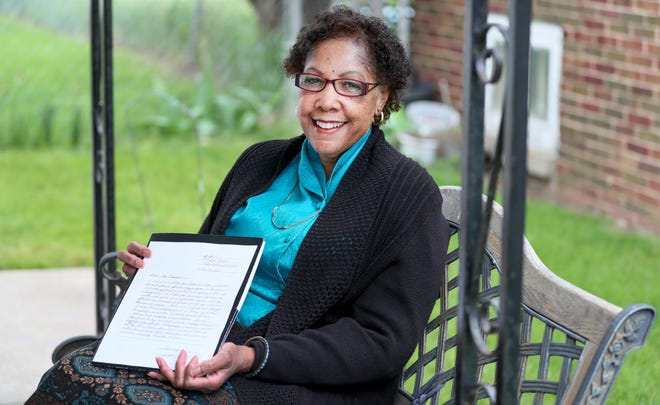 """Julia Yow, a Jehovah's Witness, poses for a portrait with a letter she wrote Friday, May 28, 2021. """"What amazes me is the changes I see that it makes in people. And despite everything that's happening, we have inner peace and a real hope for the future,"""" she said. Jehovah's Witnesses moved away from door-to-door ministry during the pandemic and turned to writing letters and making phone calls."""