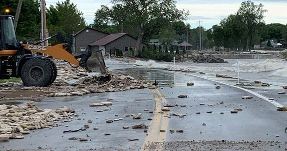A crew from the Ohio Department of Transportation in Ottawa County uses a front-end loader to clear debris from State Route 163 in Marblehead.