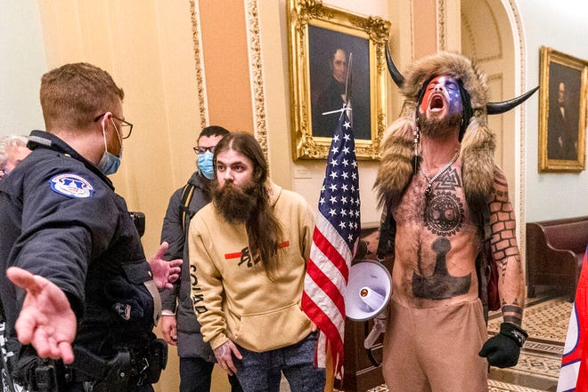 FILE - In this Jan. 6, 2021 file photo, supporters of President Donald Trump, including Jacob Chansley, right with fur hat, are confronted by U.S. Capitol Police officers outside the Senate Chamber inside the Capitol in Washington. Many of those who stormed the Capitol on Jan. 6 cited falsehoods about the election, and now some of them are hoping their gullibility helps them in court. Albert Watkins, the St. Louis attorney representing Chansley, the so-called QAnon shaman, likened the process to brainwashing, or falling into the clutches of a cult. Repeated exposure to falsehood and incendiary rhetoric, Watkins said, ultimately overwhelmed his client's ability to discern reality. (AP Photo/Manuel Balce Ceneta, File)