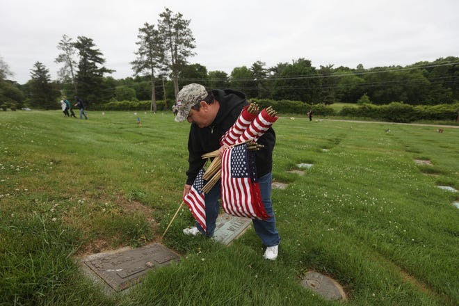 Eddie Grimes, second vice commander of Zanesville American Legion Post 29 places a flag on the grave of Ronald WIlson, who served as Petty Officer in the Navy. Grimes was one of about two dozen people who helped mark graves of veterans in preparation for Memorial Day at Zanesville Memorial Garden.