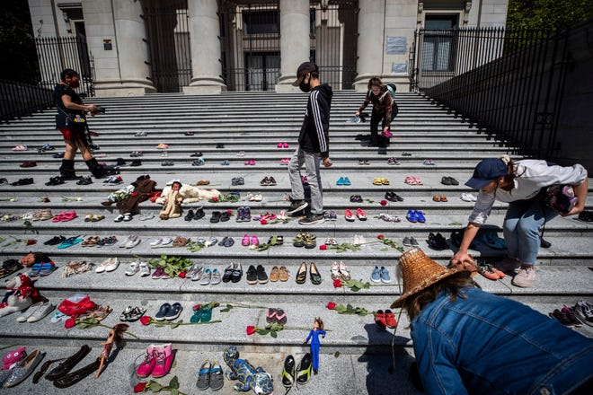 People place 215 pairs of children's shoes on the steps of the Vancouver Art Gallery as a memorial to the 215 children whose remains have been found buried at the site of a former residential school in Kamloops, in Vancouver, British Columbia, Canada on Friday, May 28, 2021.