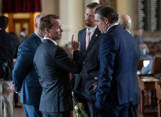 House Speaker Dade Phelan, R - Beaumont, left, talks to state representatives Will Metcalf, R - Conroe, middle, and Morgan Meyer, R - Dallas, right, before the start of debate of Senate Bill 7, at the Capitol on May 30.
