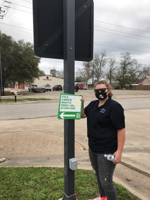 Grace Dorantes poses in Smithville with a sign that encourages residents to complete a one-mile walking route.