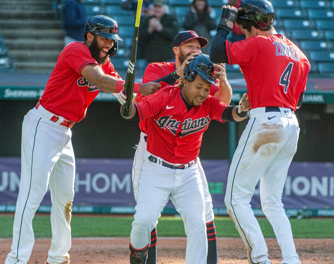 Cleveland's Amed Rosario left, along with Bradley Zimmer (4) and other teammates congratulate Jose Ramirez, center, after his winning sacrifice fly off Toronto Blue Jays relief pitcher Anthony Castro during the seventh inning of the second baseball game of a doubleheader in Cleveland, Sunday, May 30, 2021. (AP Photo/Phil Long)