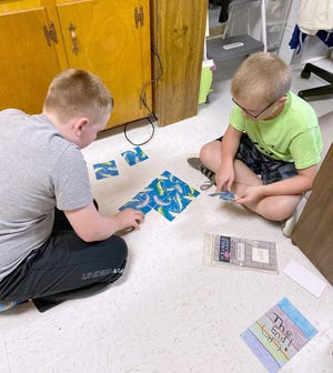 Fifth graders Jack Dwyer and Eli Austin solve a Scramble Square brain teaser puzzle.