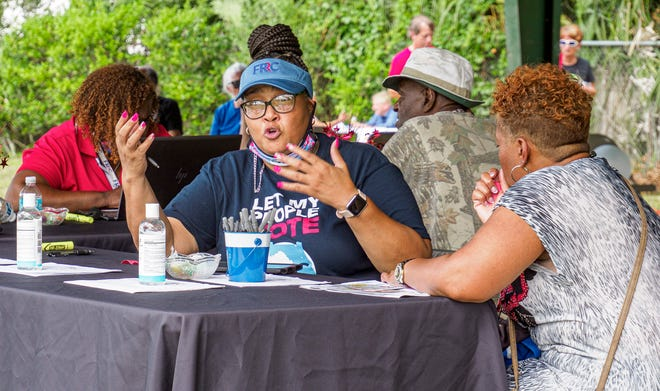 """Natalie Hays, center, speaks with a client Saturday during the """"Free the Vote"""" event at Carver Park in Eustis"""