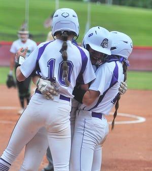 Emma Flinner hugs her sister Clowie Flinner (left) and teammate Hanna Massaro (right) after her big home run against West Branch in the regional final.
