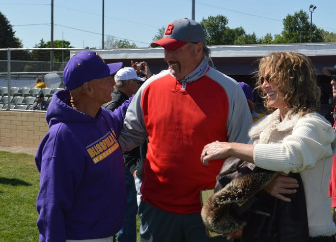 Bedford baseball coach Craig Trychel and his wife Jeni chat with Blissfield coach Larry Tuttle before ceremonies to name Blissfield's baseball field in his honor Saturday.