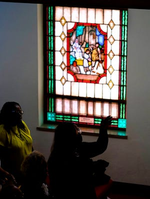 People worship Sunday near a stained glass window during the Black Wall Street Legacy Festival at the First Baptist Church of North Tulsa.