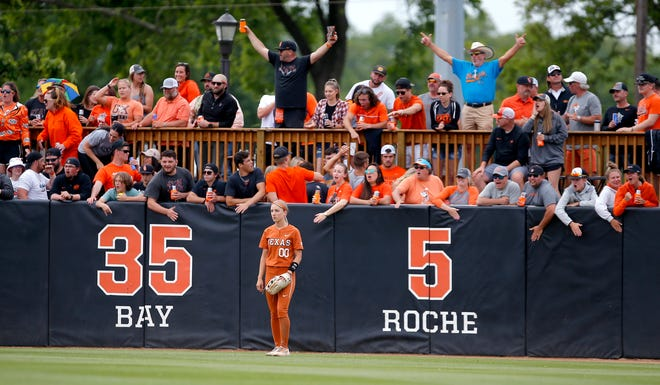 Oklahoma State fans cheer behind Texas outfielder Lauren Burke in the sixth inning of a super regional game at the Cowgirl Stadium in Stillwater, Okla., on Sunday. Oklahoma State won 2-0 and advanced to the Women's College World Series.