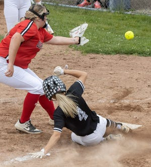 Perry's Hunter Wheeler slides under New Philadelphia pitcher Julia Miller during the fifth inning of the Division I regional final at Massillon on Sunday, May 30, 2021. (Bob Rossiter / Special to The Canton Repository)