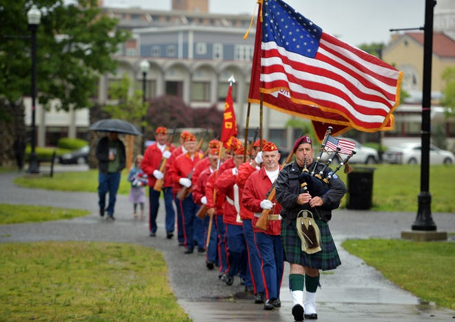 Police officer Sean Lovely leads a procession of the Worcester Detachment Marine Corps League toward the Myra Hiatt Kraft Footbridge Sunday for the traditional Water Ceremony in Elm Park in Worcester. The annual Memorial Day Weekend tradition honoring sailors, soldiers and marines from Worcester who perished at sea in service of their country.