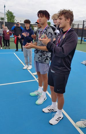 New Albany boys tennis players Devin Boyer (center) and Kaan Odabas applaud their team's second-place finish in the Ohio Tennis Coaches Association Division I state tournament. The Eagles lost to visiting Mason 3-2 in the state final May 30.
