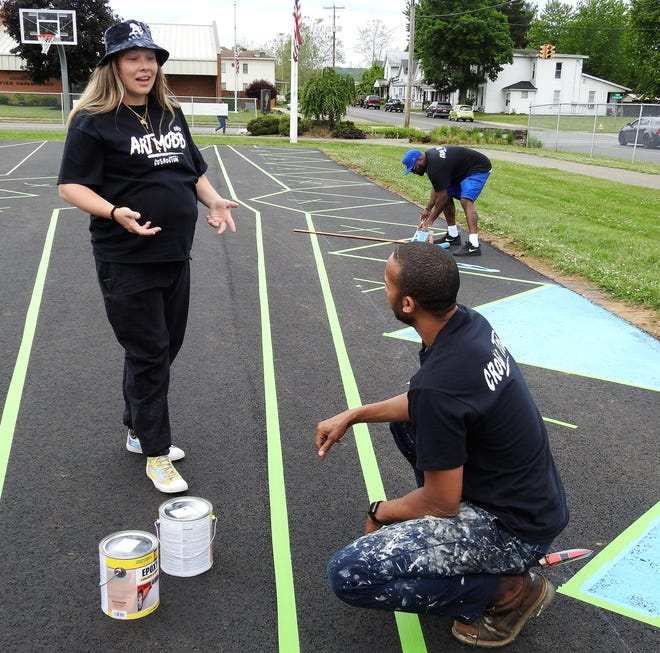 Fawn Arthur of Art Mobb talks with volunteer Nathan Gibson on their painting process as they paint a design on the basketball court at Himebaugh Park.