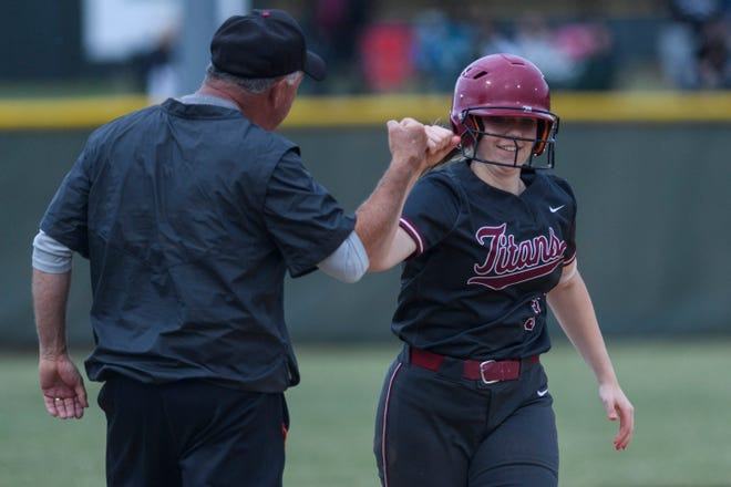 Gibson Southern coach Gary May (left) gets a fist bump from Brenna Blume (3) as she homers against Jasper in the Titans' 5-2 victory on May 29 in the Class 4A North Sectional title game.