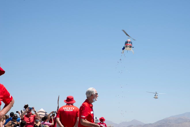 A helicopter drops red and white flowers in honor of U.S. veterans who died in major conflicts on May 30, 2021.