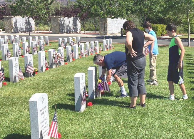 Ron Miller of Anderson places flowers at the grave of his uncle, Fred Knight, Sunday, May 30, 2021 at the Northern California Veterans Cemetery. Knight was a World War II veteran. Miller was joined by his aunt, Emily Knight and Jacob Knight and Marcus Mitchell.