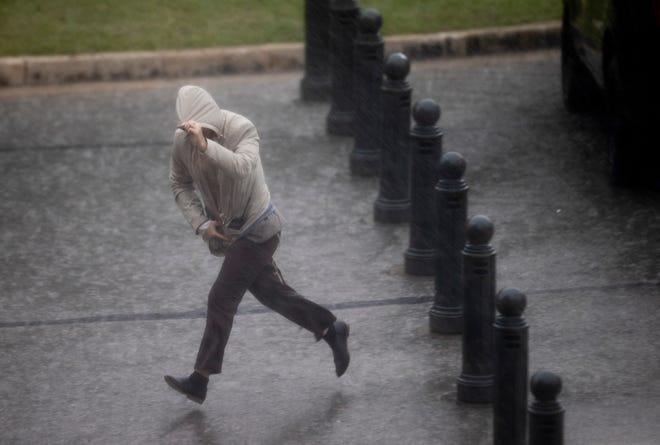Une personne traverse une averse au Capitole dimanche.