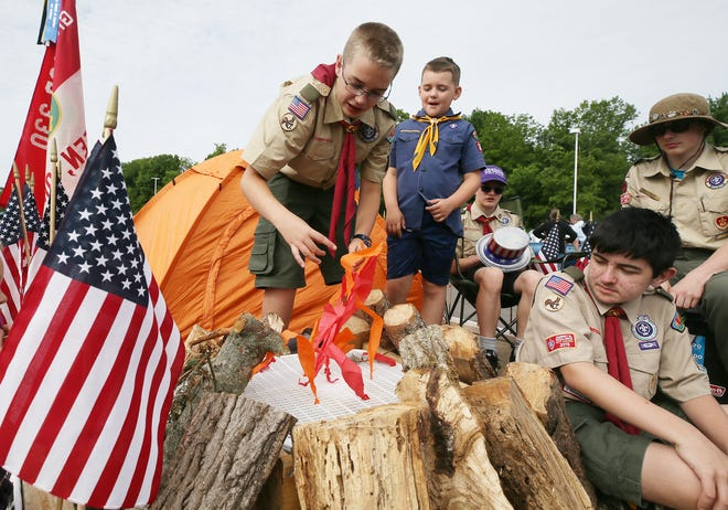 Case Spence, 11, works on the mock flames of Boy Scout Troop 330's float Monday as Colton Brewer of Cub Scout Pack 3330 looks on before the start of Green's Memorial Day Parade.