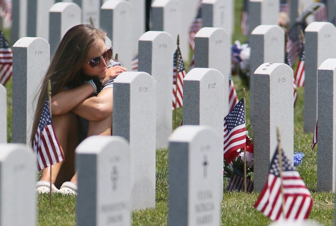 Elizabeth Spence of Cleveland visits the grave of her grandfather, U.S. Army World War II veteran Edward Spence, on Monday at Ohio Western Reserve National Cemetery in Rittman.