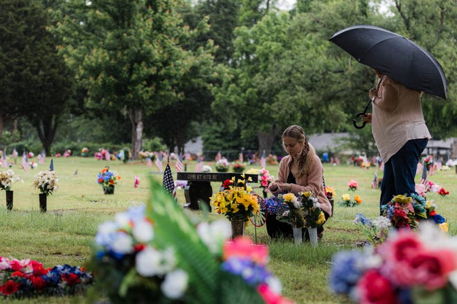 Damp Memorial Day weather didn't deter Gracie and Debbie Brashear from placing flowers on loved ones' graves at Memorial Park Cemetery in Bartlesville.