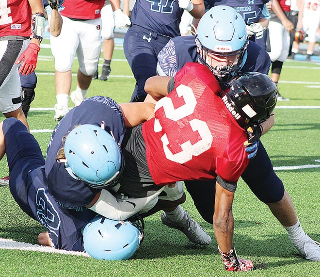 Bartlesville Bruin tacklers bury a ballcarrier during action last season.