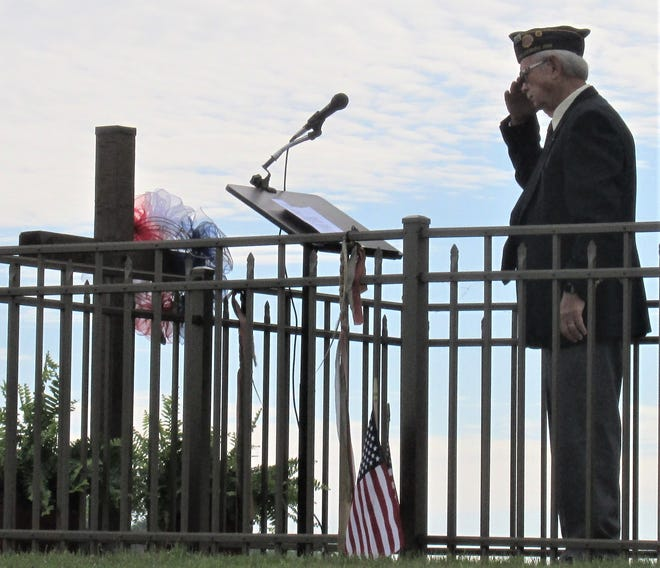 American Legion Post 192 Commander Larry Shaffer salutes after placing a wreath on the tomb of the unknown soldier at Oak Hill Cemetery in Millersburg.
