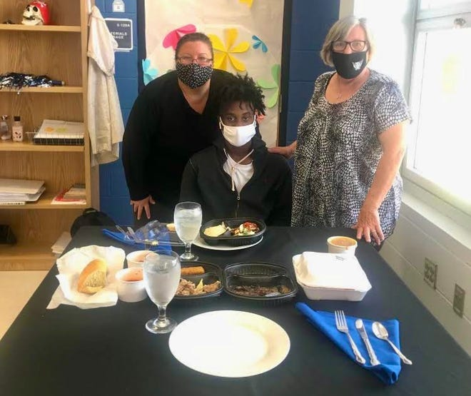 Matanzas High School senior Brad Simon and Vice Principal Sara Novak have lunch from Outback Steakhouse to celebrate Simon's accomplishments.