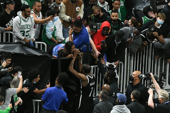Nets forward Kevin Durant (7) signs an autograph for a fan after a game against the Celtics.