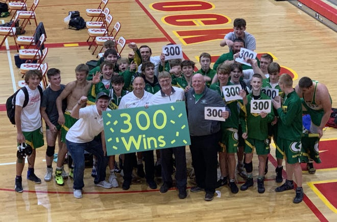 Geneseo High School Wrestling Coach Jon Murray celebrates with the team after reaching his 300th career win at the recent meet with Rock Island.